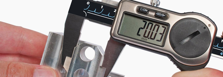 Técnico medindo peça com paquímetro